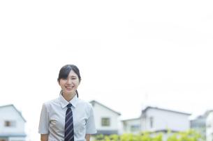 住宅街で微笑む女子学生の写真素材 [FYI03441529]