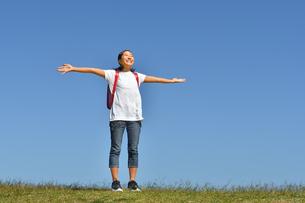 青空で両手を広げる小学生の女の子(ランドセル)の写真素材 [FYI03441693]