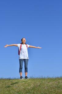 青空で両手を広げる小学生の女の子(ランドセル)の写真素材 [FYI03441694]