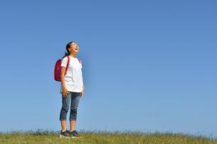 青空で見上げる小学生の女の子(ランドセル)の写真素材 [FYI03441697]