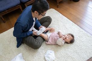 赤ちゃんのおむつ替えをする父親の写真素材 [FYI03443131]