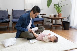 赤ちゃんのおむつを替える父親の写真素材 [FYI03443132]