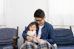 ソファーに座り赤ちゃんを膝の上に座らせている父親の写真素材 [FYI03443135]