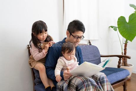 子供に絵本を読んであげる父親の写真素材 [FYI03443142]