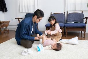 おむつを替える父親とそれを手伝う女の子の写真素材 [FYI03443144]