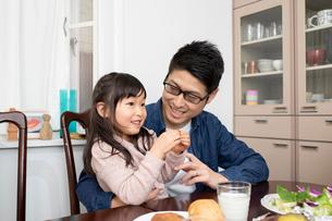 父親の膝の上に座り食事をする女の子の写真素材 [FYI03443161]