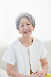 ソファに座る笑顔の女性の写真素材 [FYI03443348]