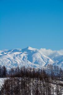 青空と冬山の山頂 十勝岳の写真素材 [FYI03443433]