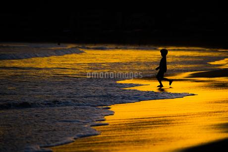 夕暮れの波打ち際で遊ぶ子供の写真素材 [FYI03444638]