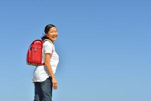 青空で笑う小学生の女の子(ランドセル)の写真素材 [FYI03444670]