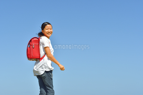 青空で笑う小学生の女の子(ランドセル)の写真素材 [FYI03444671]