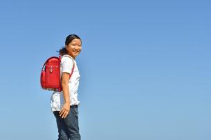 青空で笑う小学生の女の子(ランドセル)の写真素材 [FYI03444672]