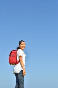 青空で笑う小学生の女の子(ランドセル)の写真素材 [FYI03444673]