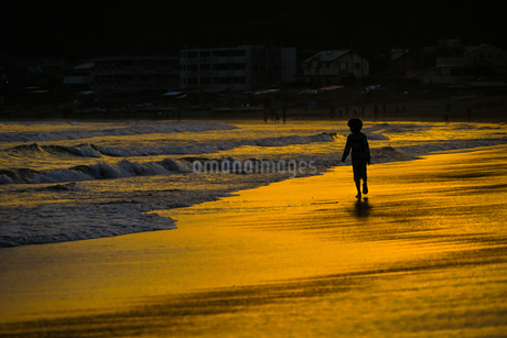 夕暮れの波打ち際で遊ぶ子供の写真素材 [FYI03444773]