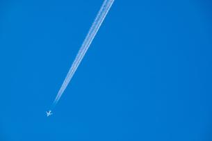 青空の下の飛行機と飛行機雲の写真素材 [FYI03445455]