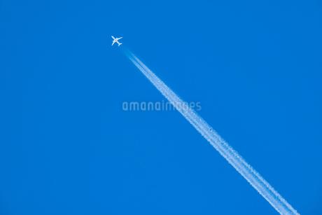 青空の下の飛行機と飛行機雲の写真素材 [FYI03445456]
