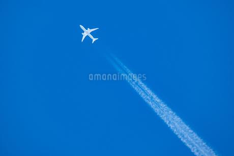 青空の下の飛行機と飛行機雲の写真素材 [FYI03445457]