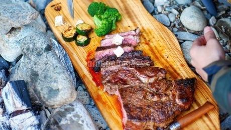 キャンプ場で焼いたステーキを盛り付けるの写真素材 [FYI03445811]