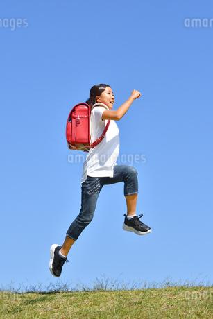青空でジャンプする女の子(ランドセル)の写真素材 [FYI03445812]