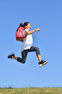 青空でジャンプする女の子(ランドセル)の写真素材 [FYI03445813]