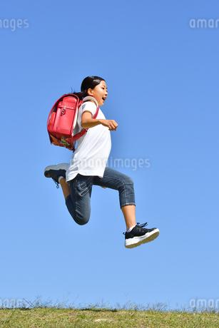 青空でジャンプする女の子(ランドセル)の写真素材 [FYI03445814]