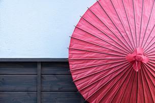 赤い和傘と白塗りの壁の写真素材 [FYI03447135]