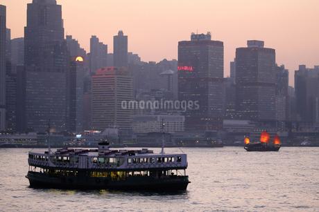 夕暮れのビクトリア湾を航行するスターフェリー(手前)と観光クルーズ船「アクアルナ」(奥)の写真素材 [FYI03447496]