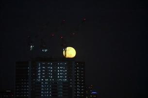 高層ビルの上に浮かぶ満月の写真素材 [FYI03447628]