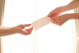 白い手紙を渡す女性の手01の写真素材 [FYI03448110]