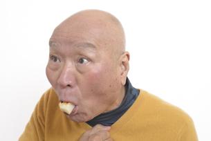 老人が餅を喉に詰まらせて苦しむの写真素材 [FYI03448422]