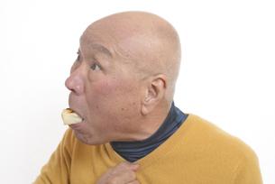老人が餅を喉に詰まらせて苦しむの写真素材 [FYI03448423]