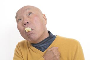 老人が餅を喉に詰まらせて苦しむの写真素材 [FYI03448424]