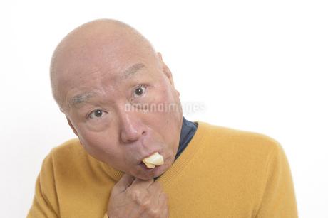 老人が餅を喉に詰まらせて苦しむの写真素材 [FYI03448425]