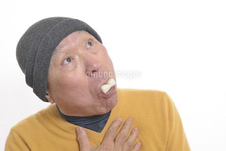 老人が餅を喉に詰まらせて苦しむの写真素材 [FYI03448426]