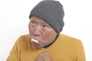 老人が餅を喉に詰まらせて苦しむの写真素材 [FYI03448427]