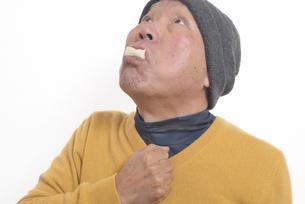 老人が餅を喉に詰まらせて苦しむの写真素材 [FYI03448428]