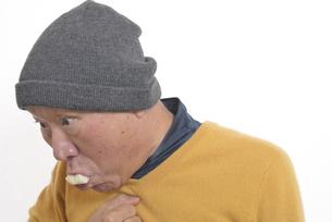老人が餅を喉に詰まらせて苦しむの写真素材 [FYI03448430]
