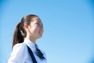 遠くを見て笑っている制服姿の女子学生の写真素材 [FYI03448913]