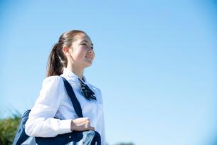 遠くを見て笑っている制服姿の女子学生の写真素材 [FYI03448915]