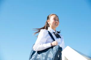 遠くを見て笑っている制服姿の女子学生の写真素材 [FYI03448993]