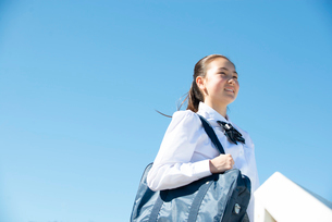 遠くを見て笑っている制服姿の女子学生の写真素材 [FYI03449252]