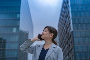 スマートフォンで話すビジネスウーマンの写真素材 [FYI03449826]