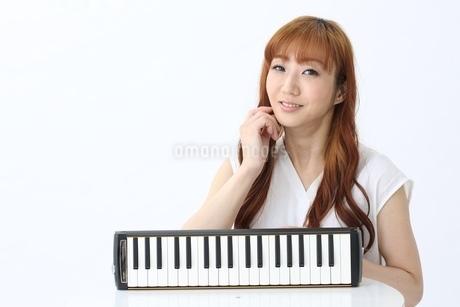 鍵盤ハーモニカと笑う女性の写真素材 [FYI03451408]