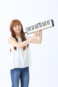 鍵盤ハーモニカを持つ女性の写真素材 [FYI03451409]
