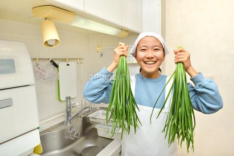 キッチンで野菜を持つ女の子の写真素材 [FYI03451489]