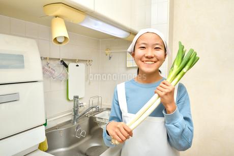 キッチンで野菜を持つ女の子の写真素材 [FYI03451492]