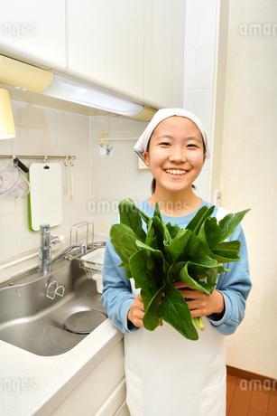 キッチンで野菜を持つ女の子の写真素材 [FYI03451498]