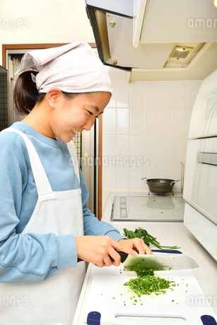 キッチンで料理をする女の子の写真素材 [FYI03451627]