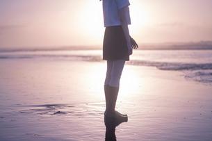 女子高生 海 後ろ姿 足元 輝きの写真素材 [FYI03451877]