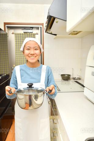 キッチンで笑う女の子の写真素材 [FYI03452309]